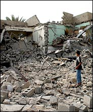 Young Iraqi boy examines rubble at a bombing site in Falluja
